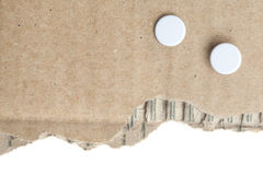 Piece of cardboard with punch holes. Cardboard ripped from a carton with two punch holes Stock Images