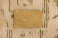 Piece of cardboard on tattered corrugated cardboard background. Stock Photography