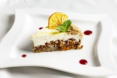 The piece of carrot cake with cream, nuts and dried orange Royalty Free Stock Images