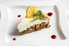 The piece of carrot cake with cream, nuts and dried orange Stock Photo
