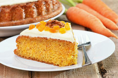 Piece of carrot cake with icing decorated dried apricots and wal Royalty Free Stock Photography
