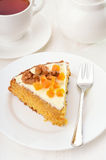 Piece of carrot cake with icing on white plate Stock Image