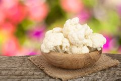 Piece of cauliflower in bowl on wooden table with blurred garden background.  Royalty Free Stock Photography