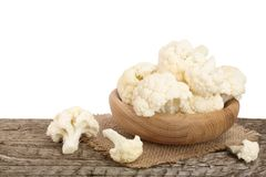 Piece of cauliflower in bowl on wooden table with white background.  Royalty Free Stock Images