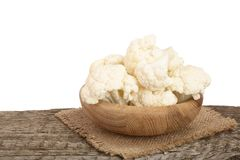 Piece of cauliflower in bowl on wooden table with white background.  Royalty Free Stock Photo