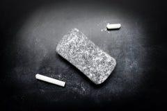 Piece of chalk and eraser on blackboard. Piece of White chalk and eraser on blackboard Stock Photography