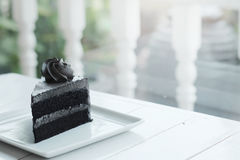A piece of charcoal cake on white wooden table. Have some space foe write wording stock image