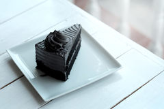 A piece of charcoal cake on white wooden table. Have some space foe write wording royalty free stock images