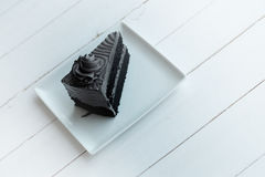 A piece of charcoal cake on white wooden table. Have some space foe write wording Royalty Free Stock Photo