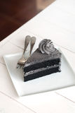 A piece of charcoal cake on white wooden table. Have some space foe write wording royalty free stock image