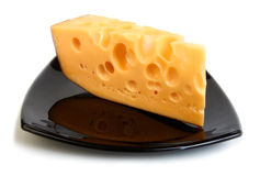 Piece of cheese on black plate Stock Photography