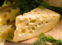 Piece of cheese with dill on wooden table Royalty Free Stock Image