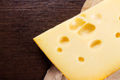 Piece of cheese lies on the dark brown wooden table Royalty Free Stock Images