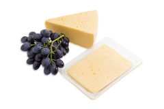 Piece of cheese, sliced cheese and bunch of grapes Royalty Free Stock Photos