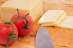 Piece of cheese and slices of cheese with  tomatoes on a wodden Royalty Free Stock Photos
