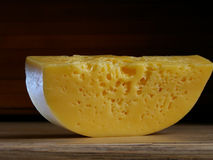 A piece of cheese on the table. One piece of cheese on a wooden table Stock Photo