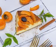 Piece of cheesecake with apricots on a white wooden board Royalty Free Stock Photos