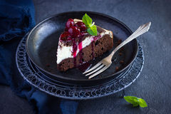 Piece of cheesecake brownie cake with cherry sauce Royalty Free Stock Photo