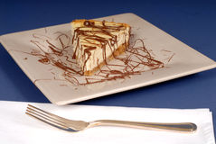 A piece of cheesecake with chocolate drizzled over it with fork Royalty Free Stock Photos
