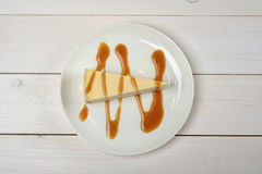 A piece of cheesecake, drizzled in caramel sauce on a white plate standing on wooden white table. The view from the top. Rich piece of cheesecake, drizzled in Royalty Free Stock Image