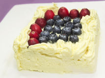 Piece of cheesecake with forest berries , blueberries and cranberries on withe plate Royalty Free Stock Photo