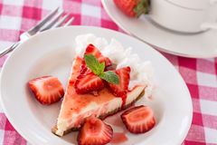 Piece of Cheesecake With Fresh Sliced Strawberries With Fork. Piece of cheesecake with fresh sliced strawberries on red checkered cloth with fork Royalty Free Stock Photos