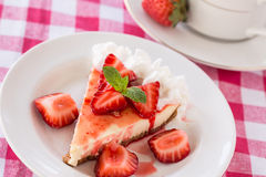 Piece of Cheesecake With Fresh Sliced Strawberries. On red checkered cloth with coffee cup Royalty Free Stock Photography