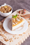 Piece of cheesecake with nut on wooden board. Piece of cheesecake on wooden board,  close-up, vertical Stock Photography