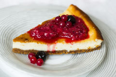 Piece of cheesecake with red and black berries on top of it on white plate Royalty Free Stock Images