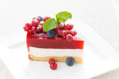 Piece of cheesecake with strawberry jelly on a plate, close-up Royalty Free Stock Images