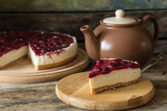Piece of cheesecake with teapot on wooden table Stock Photo