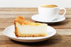 Piece of a cheesecake on a white saucer and cup of coffee Stock Photos