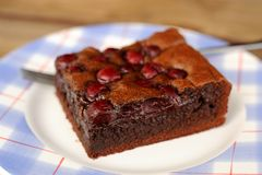 A piece of cherry brownie. On checked blue plate Royalty Free Stock Photo