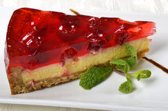 A piece of cherry cheese cake. A piece of cherry cheese cake with cherry jelly on top and a leave of mint Royalty Free Stock Photography