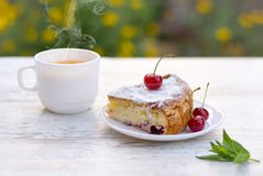 A piece of cherry pie and hot tea with lemon and mint. A delicious piece of cherry pie on a white plate and a white cup of hot tea with lemon and mint stock images