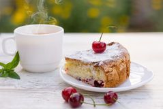 A piece of cherry pie and hot tea with lemon and mint. A delicious piece of cherry pie on a white plate and a white cup of hot tea with lemon and mint. close-up royalty free stock photography