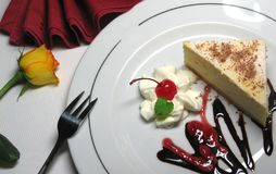 Piece of chessecake. Piece of cheesecake with fruits with whipped cream  on the plate Royalty Free Stock Images