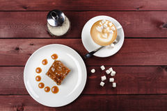 A piece of chocolate brownie and caramel sauce, a cup of cappuccino on a white plate. Top view. A piece of tasty chocolate brownie and caramel sauce, a cup of Royalty Free Stock Photos