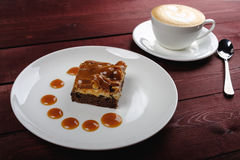 A piece of chocolate brownie and caramel sauce, a cup of cappuccino on a white plate. Top view. A piece of tasty chocolate brownie and caramel sauce, a cup of Stock Photo