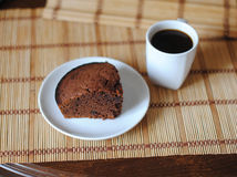 A piece of chocolate brownies and coffee in a white bowl on a mat. Close-up Stock Photos