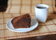 A piece of chocolate brownies and coffee in a white bowl on a mat. Close-up Royalty Free Stock Image