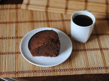 A piece of chocolate brownies and coffee in a white bowl on a mat. Close-up Stock Images