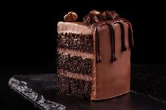 Piece of chocolate cake. Chocolate mousse cake slice on a black board, black background. Chocolate Treat stock images