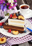 Piece of chocolate cake with cream and fresh fruit. Piece of chocolate layer cake with cream and fresh fruit Royalty Free Stock Photo