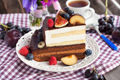Piece of chocolate cake with cream and fresh fruit. Piece of chocolate layer cake with cream and fresh fruit Royalty Free Stock Photography