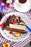 Piece of chocolate cake with cream and fresh fruit. Piece of chocolate layer cake with cream and fresh fruit Royalty Free Stock Image