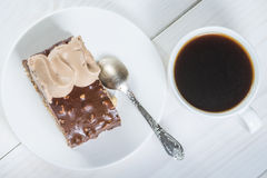 Piece of chocolate cake and cup of coffee on a background of whi. Piece of chocolate cake and cup of coffee on a background of wood Royalty Free Stock Photos