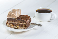 Piece of chocolate cake and cup of coffee on a background of whi. Piece of chocolate cake and cup of coffee on a background of wood Royalty Free Stock Images