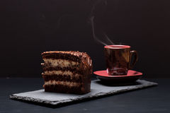 A piece of chocolate cake and cup of coffee on slate plate on bl Stock Photography