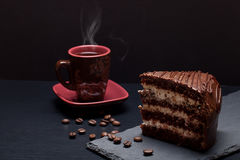 Piece of chocolate cake and cup of coffee on slate plate on blac Royalty Free Stock Photo